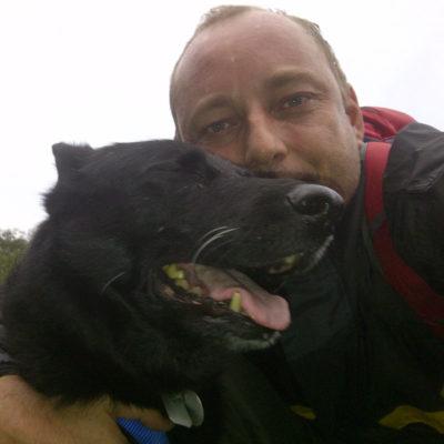 Ein schwarzer deutscher Schäferhund aus dem Tierheim mit seinem neuen Besitzer. Hundefreund in der Natur beim Wandern.